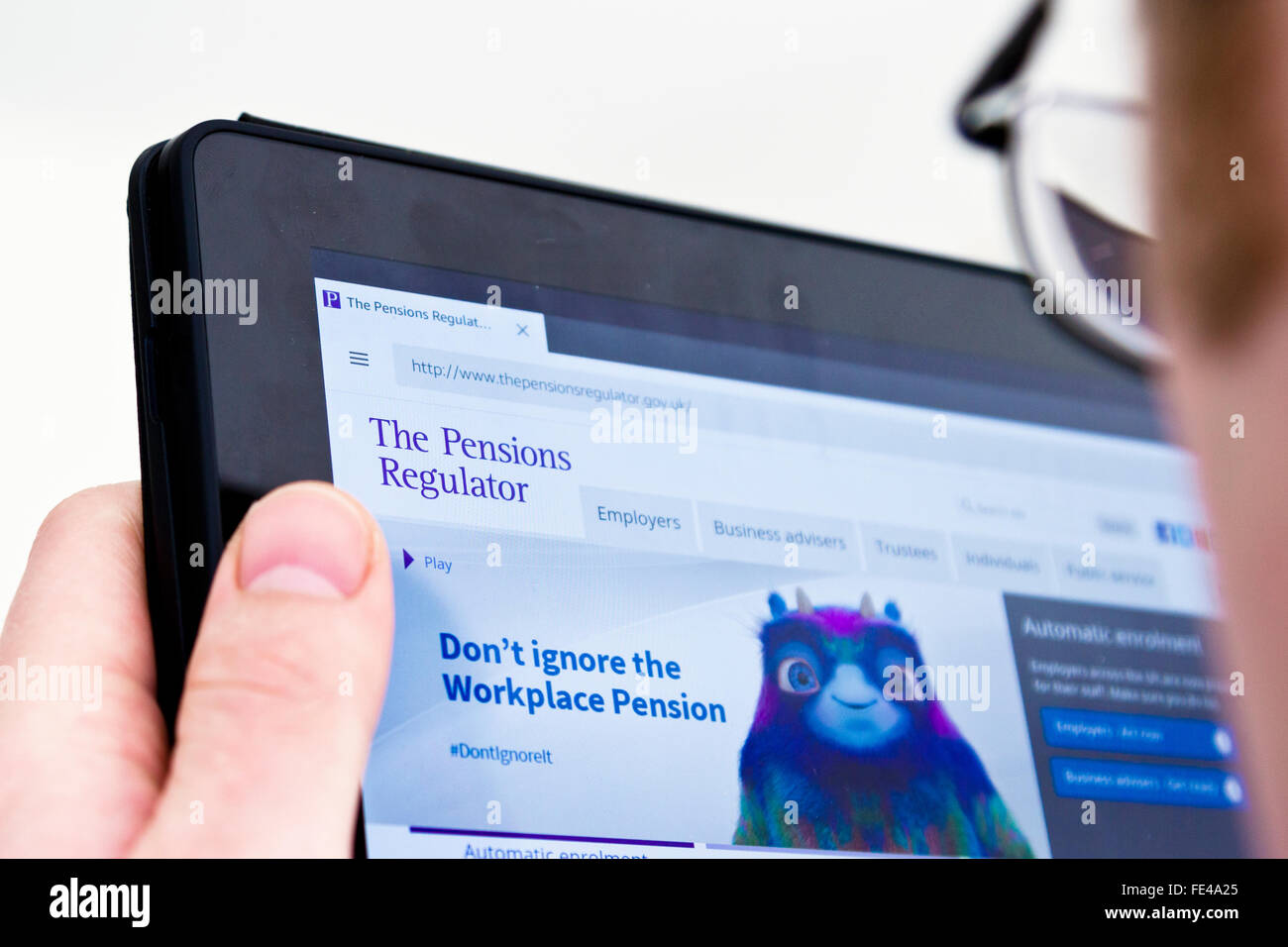 Employer looking at information about the UK government's Pensions Regulator - Stock Image