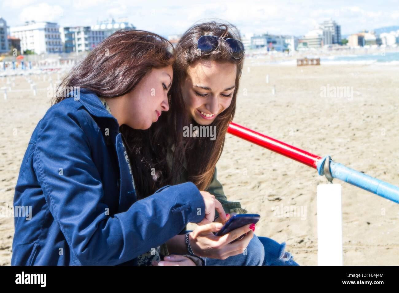 Female Friends Text Messaging On The Beach - Stock Image