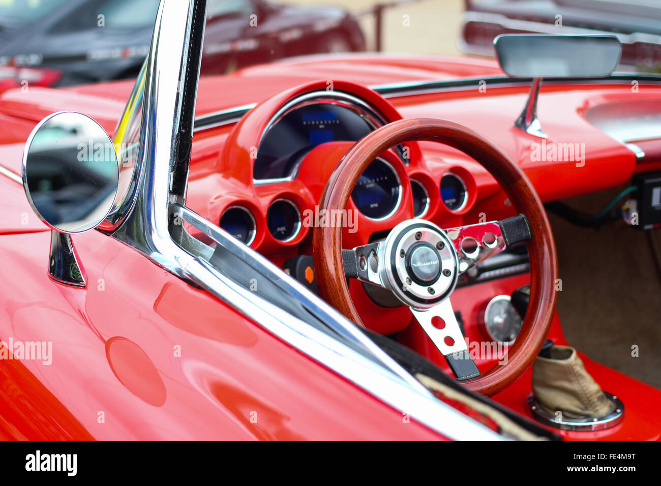 An early 60's convertible red Chevrolet Corvette's steering wheel and panel at a car showdown - Stock Image