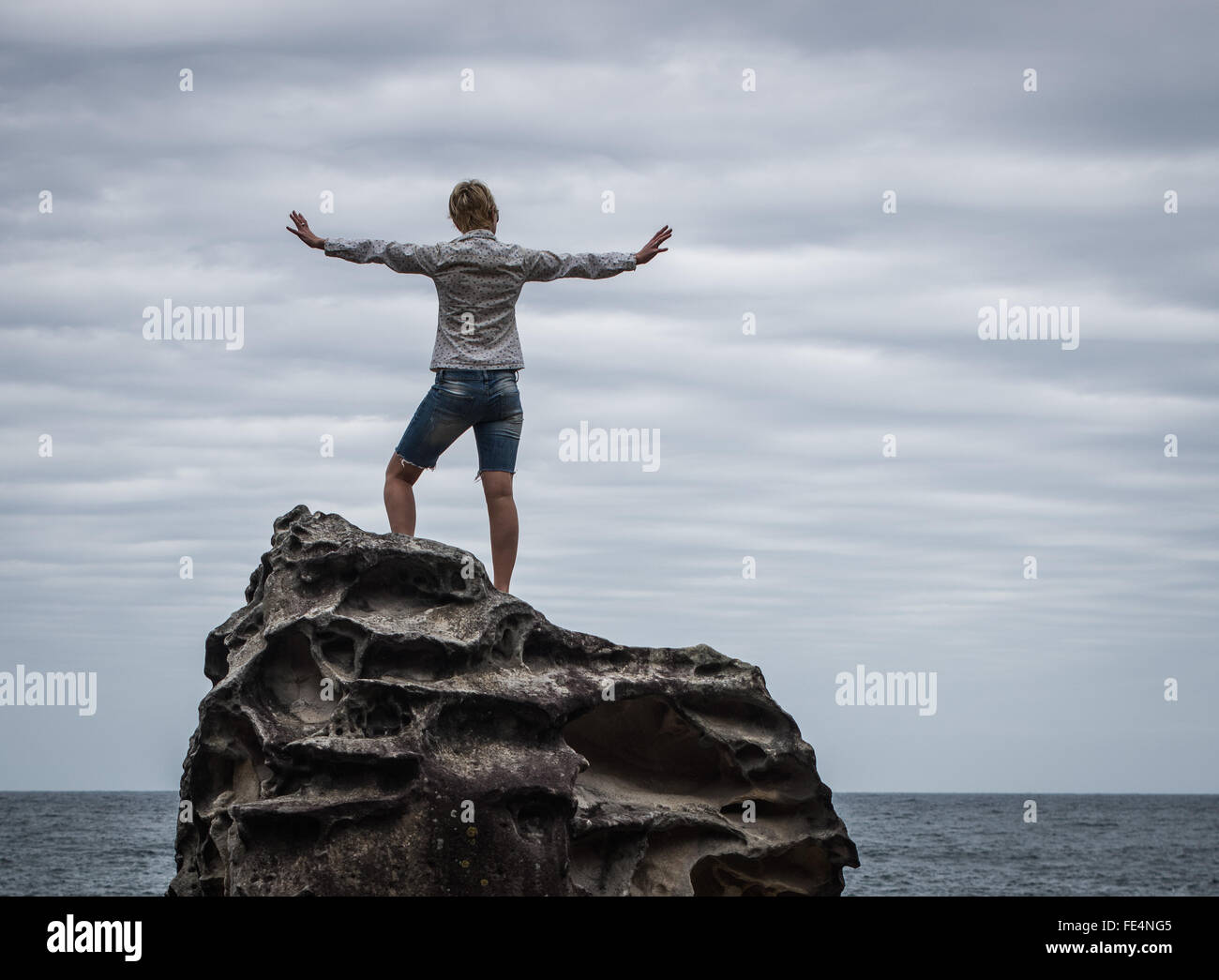 Woman Standing At The Coast With Her Arms Outstretched - Stock Image