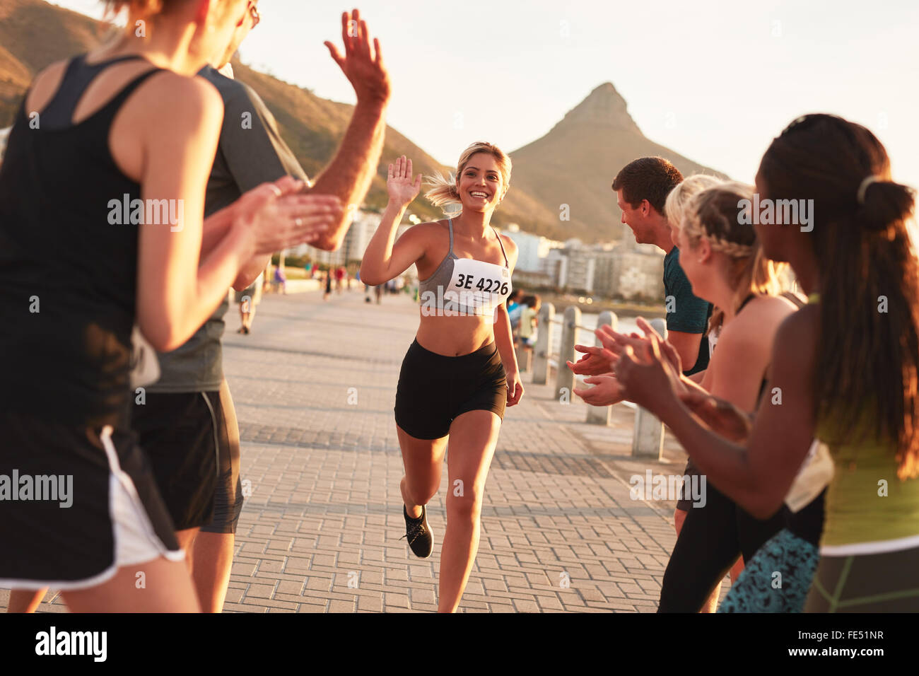 Group of spectators cheering runners just before the finish line. Female runner finishing the race with her team - Stock Image