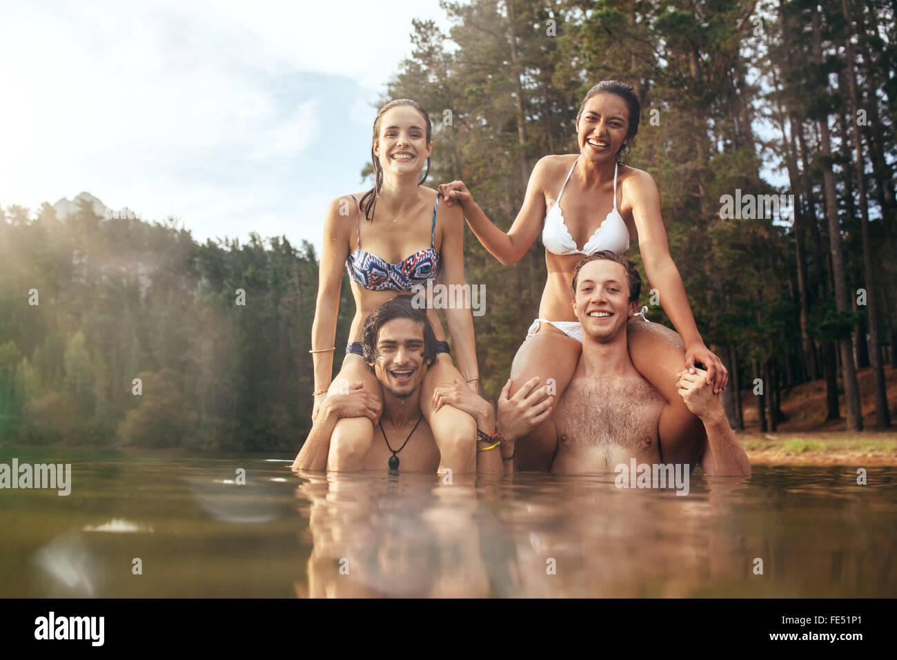 Portrait of young  men carrying their girlfriends on shoulders. Happy young couples enjoying a day at the lake. - Stock Image