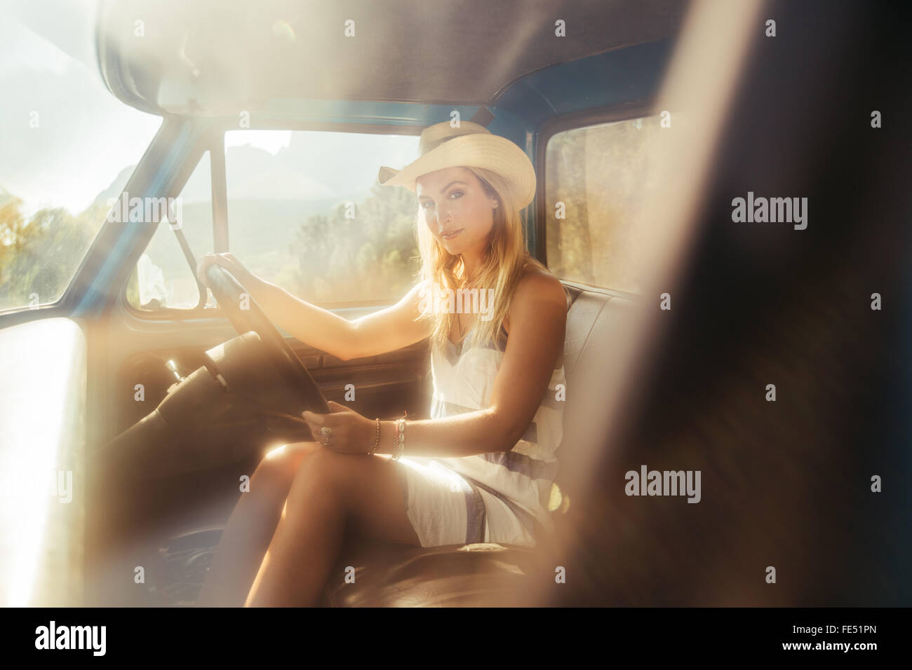 Portrait of an attractive young woman wearing a hat driving a car on sunny day - Stock Image