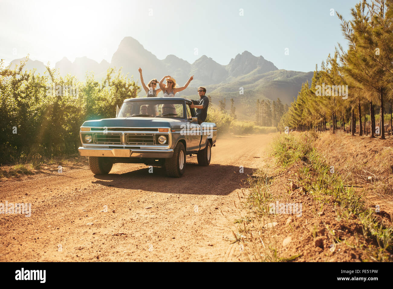 Friends having fun in the open back of a vintage truck on a summer day in countryside. Young men and woman enjoying - Stock Image