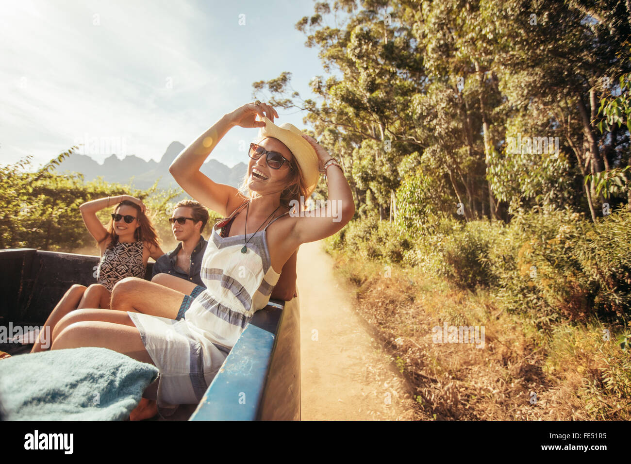 Portrait of a cheerful young woman sitting in the back of pickup truck with friends. Young people enjoying on a - Stock Image
