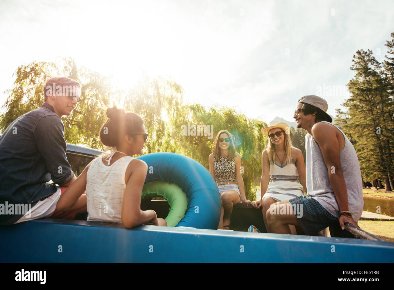 Group of young friends sitting in the back of a pickup truck with inflatable tubes going on a summer holidays on Stock Photo