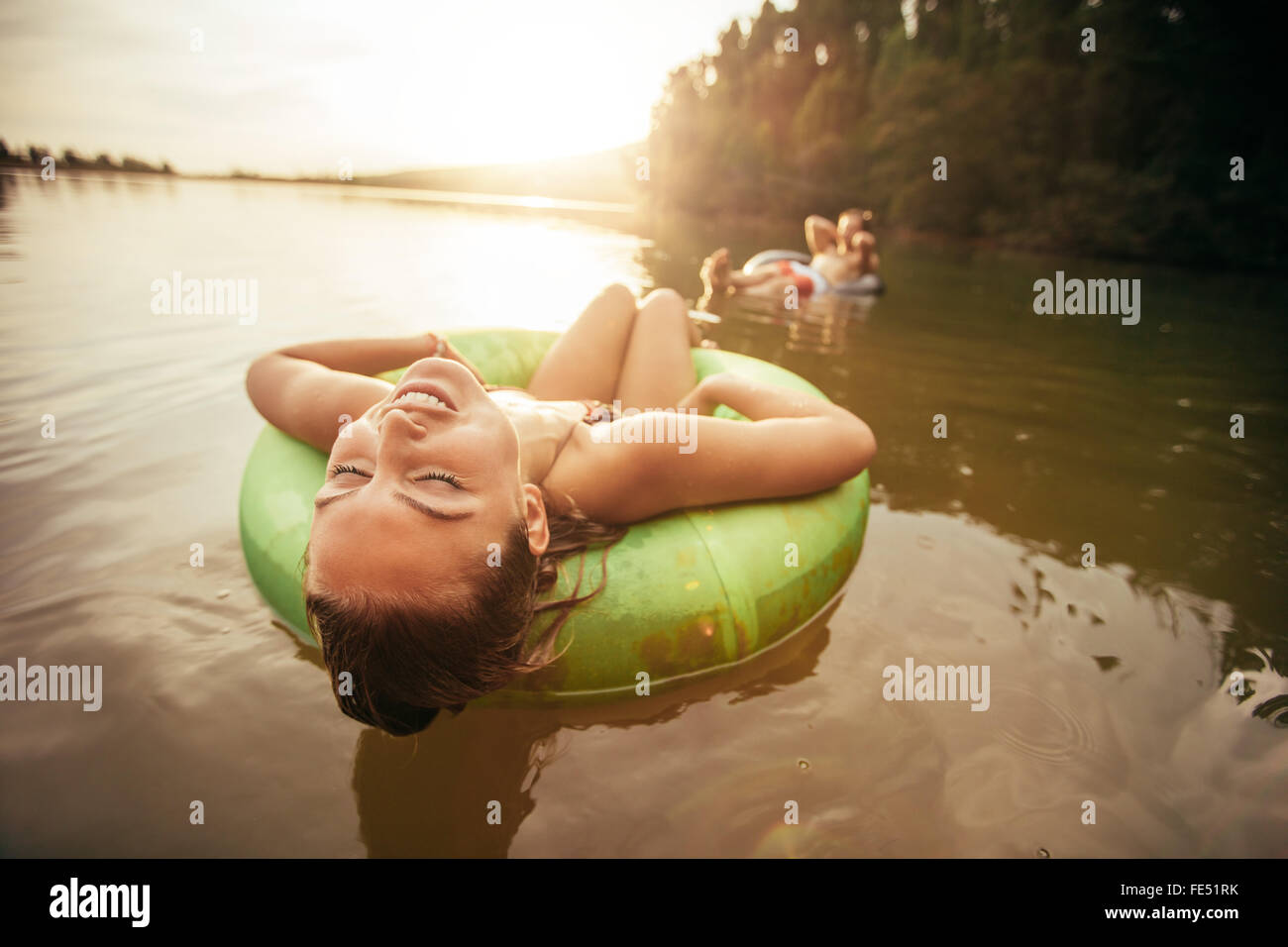 Closeup portrait of young woman with her eyes closed relaxing on inflatable ring in lake on a sunny day. - Stock Image