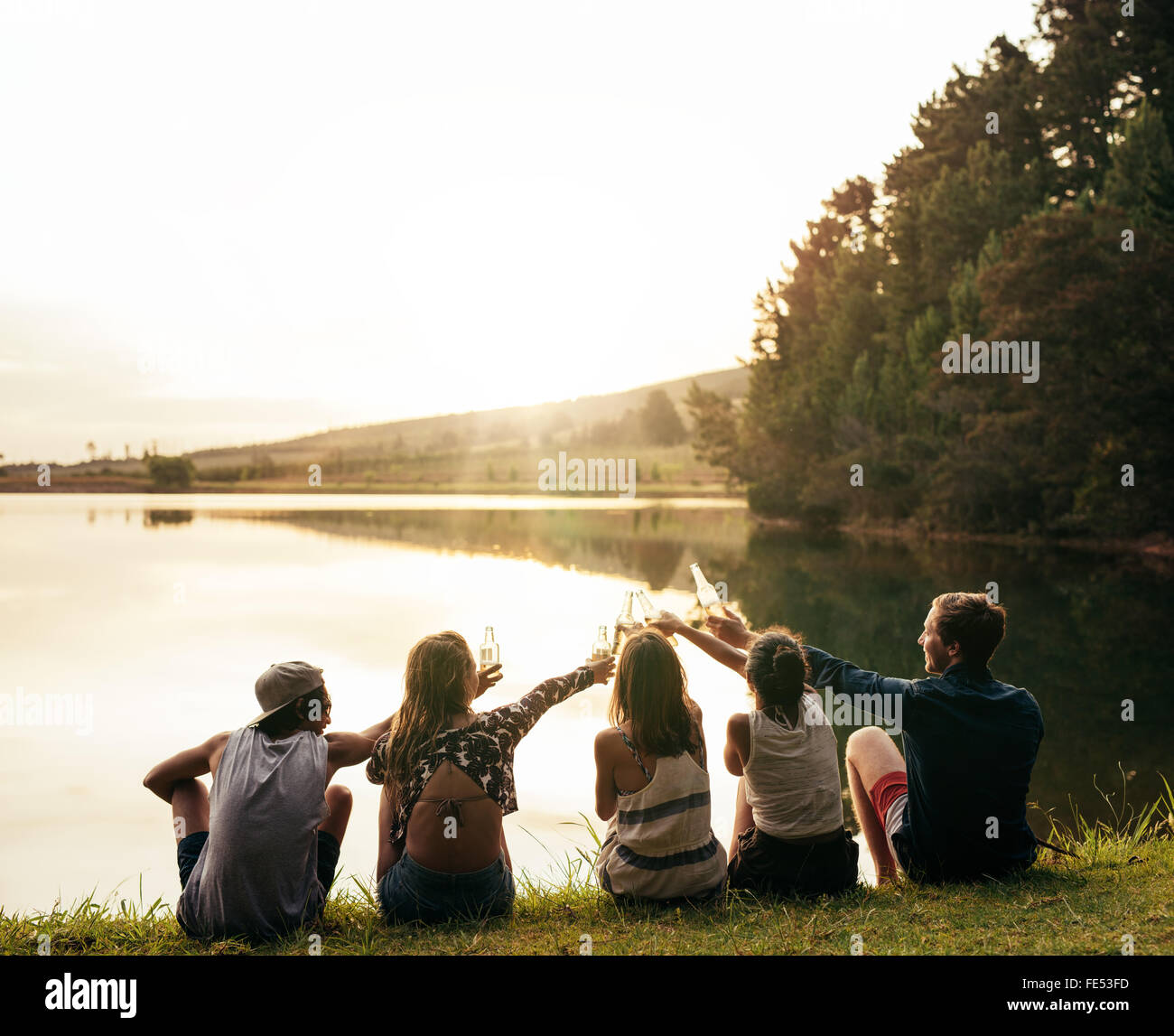 Group of young people sitting in a row at a lake. Young friends toasting and celebrating with beers at the lake. - Stock Image
