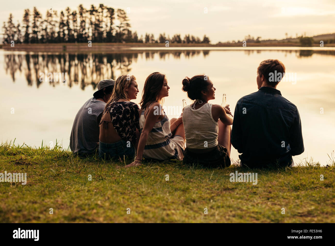 Rear view portrait of group of young friends relaxing by a lake. Young people sitting together by a lake. - Stock Image