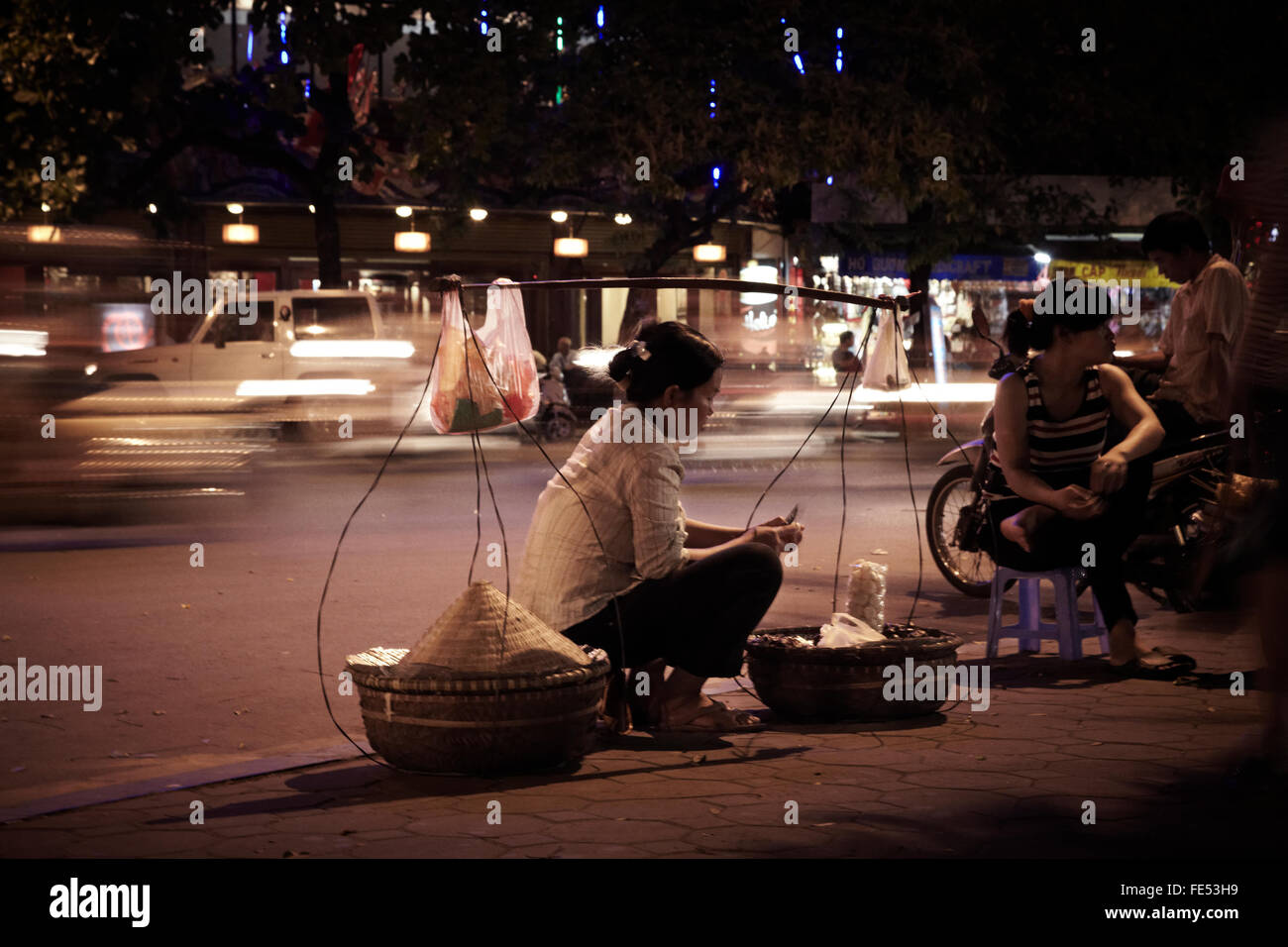 saleswoman in street in Hanoi, to the borderline of the street at night in Hanoi, Vientam - Stock Image