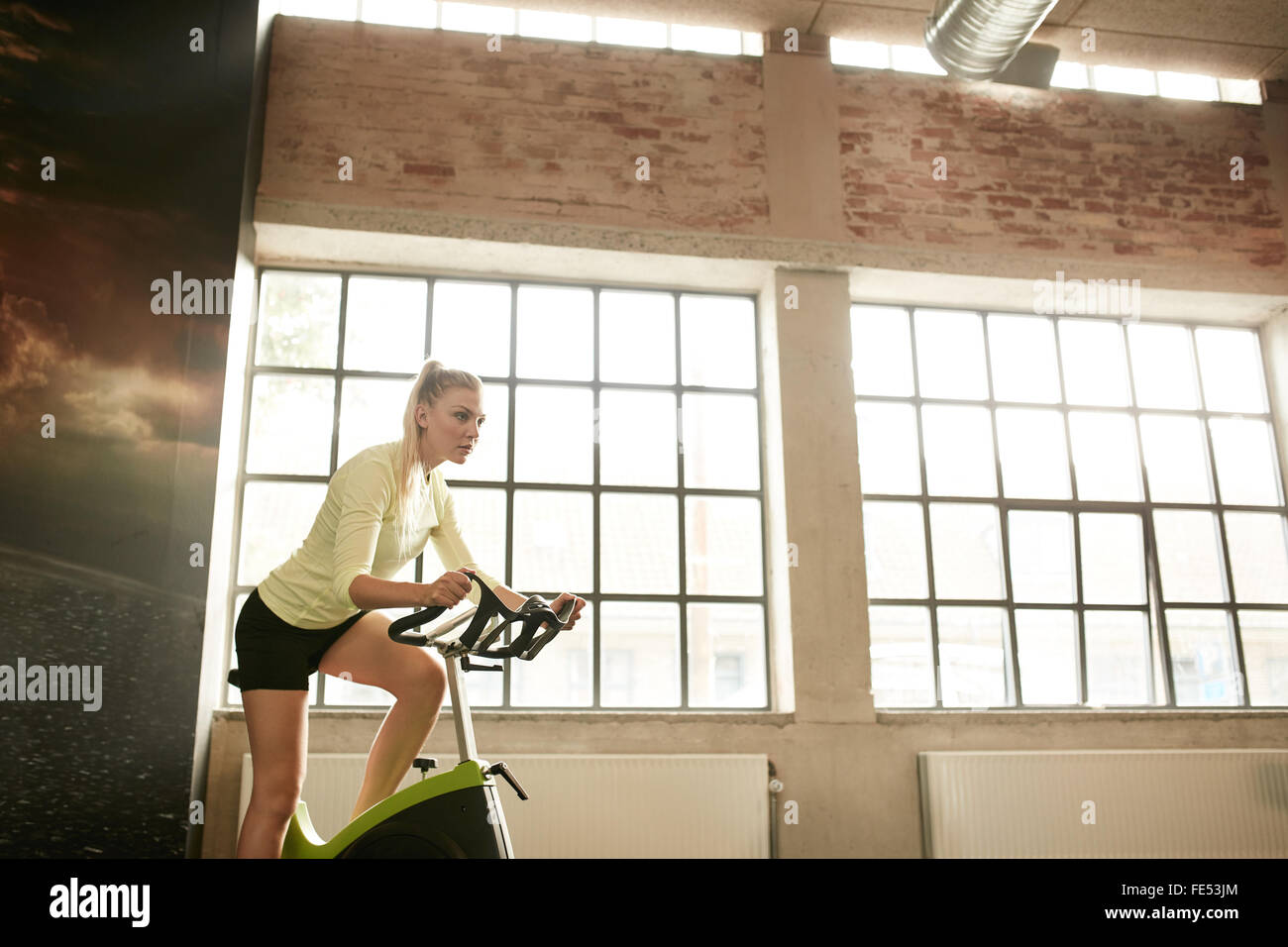 Fitness woman exercising on a spinning cycle in gym. Caucasian young female athlete doing fitness training on a - Stock Image