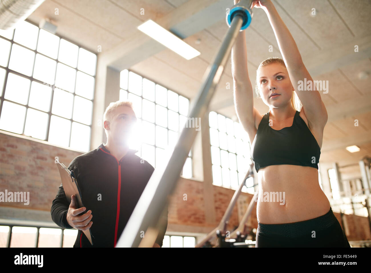 Female working out with her personal trainer in gym. Young woman exercising with a barbell in the gym with her fitness - Stock Image