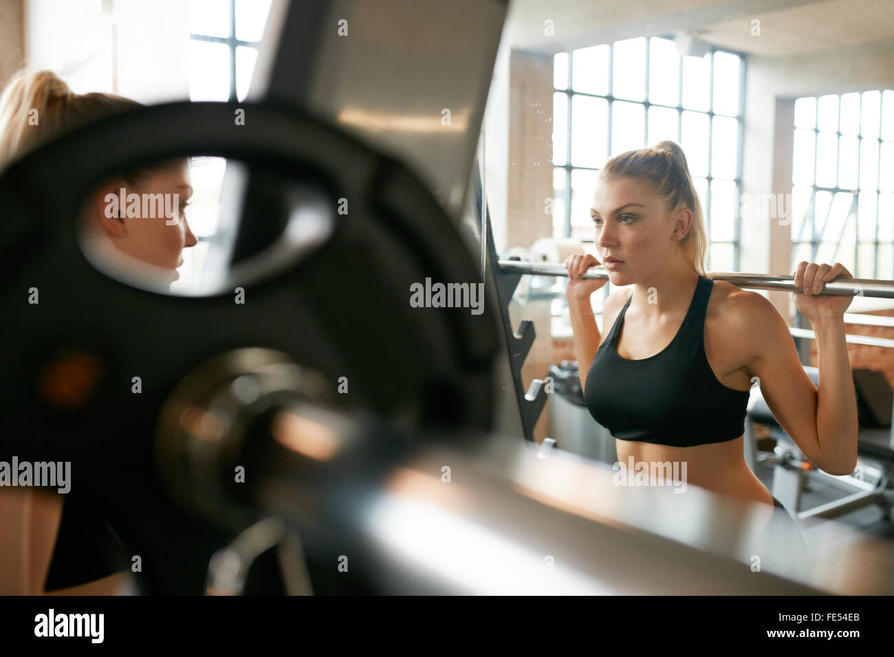 Young woman in gym doing squats with extra weight on shoulders. Fitness female working out in front of mirror at - Stock Image
