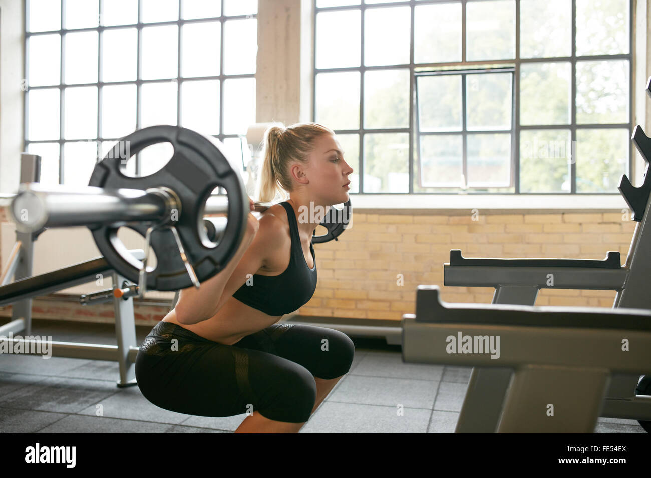 Female working out in a gym doing squats. Young woman working out using barbell with heavy weights in a fitness - Stock Image