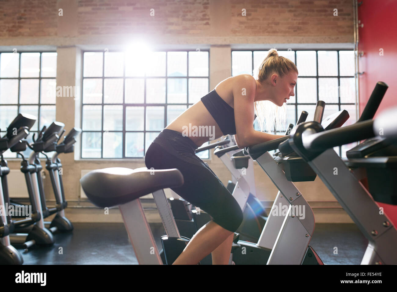 Young woman working out on exercise bike at the gym. Indoor shot of a female doing fitness training on stationary - Stock Image