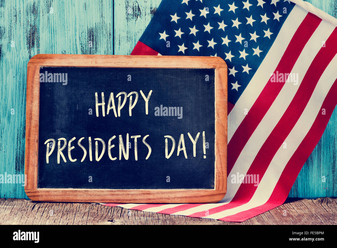 the text happy presidents day written in a chalkboard and a flag of the United States, on a rustic wooden background - Stock Image