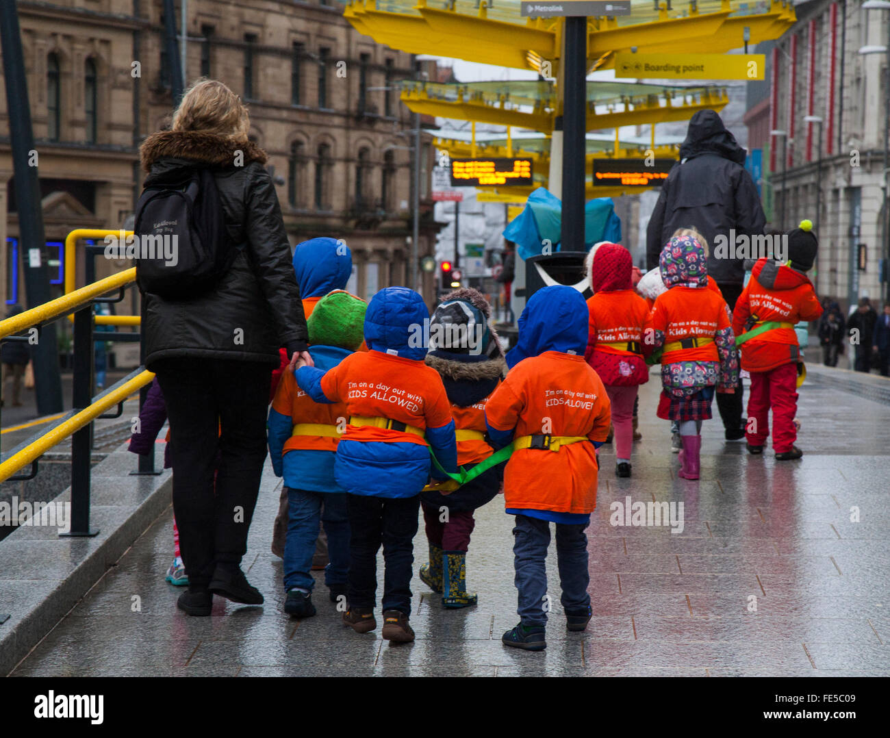 School children safeguarded, wearing protective fluorescent hi-vis hazard jackets during the Chinese New Year, Manchester, - Stock Image