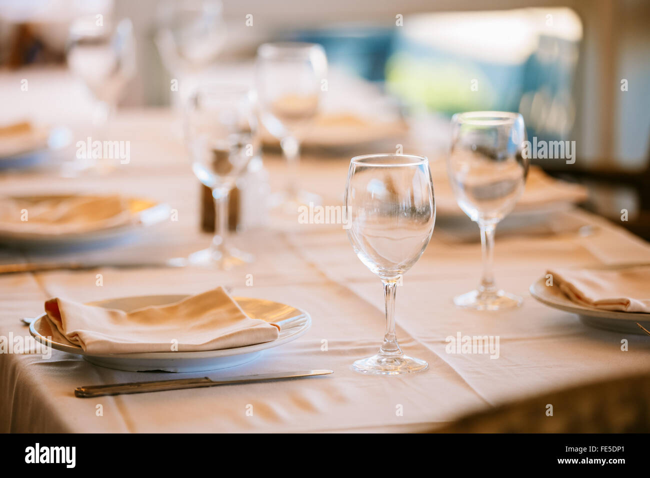 The cozy interior of the summer cafe European city. Tableware, tables covered with tablecloths. Resting-place. Catering. - Stock Image