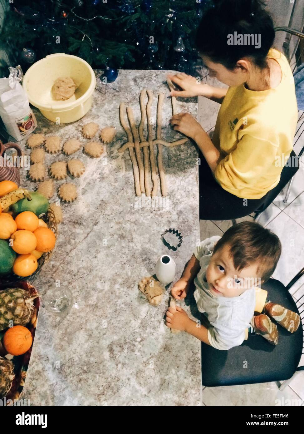 High Angle View Of Son Helping Mother In Preparing Food On Table - Stock Image