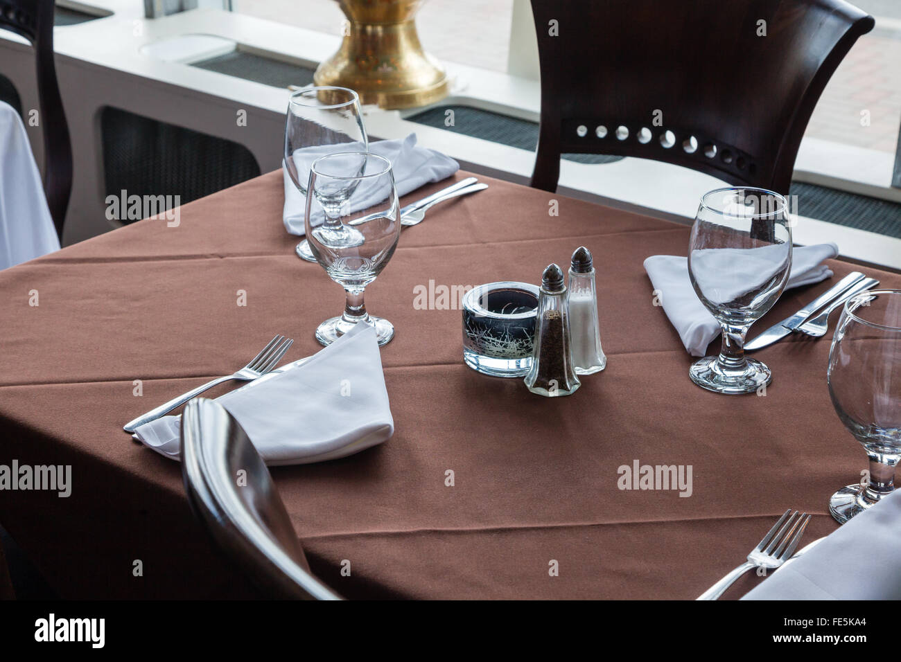 Casual table for two setting with brown table cloth and glassware. - Stock Image