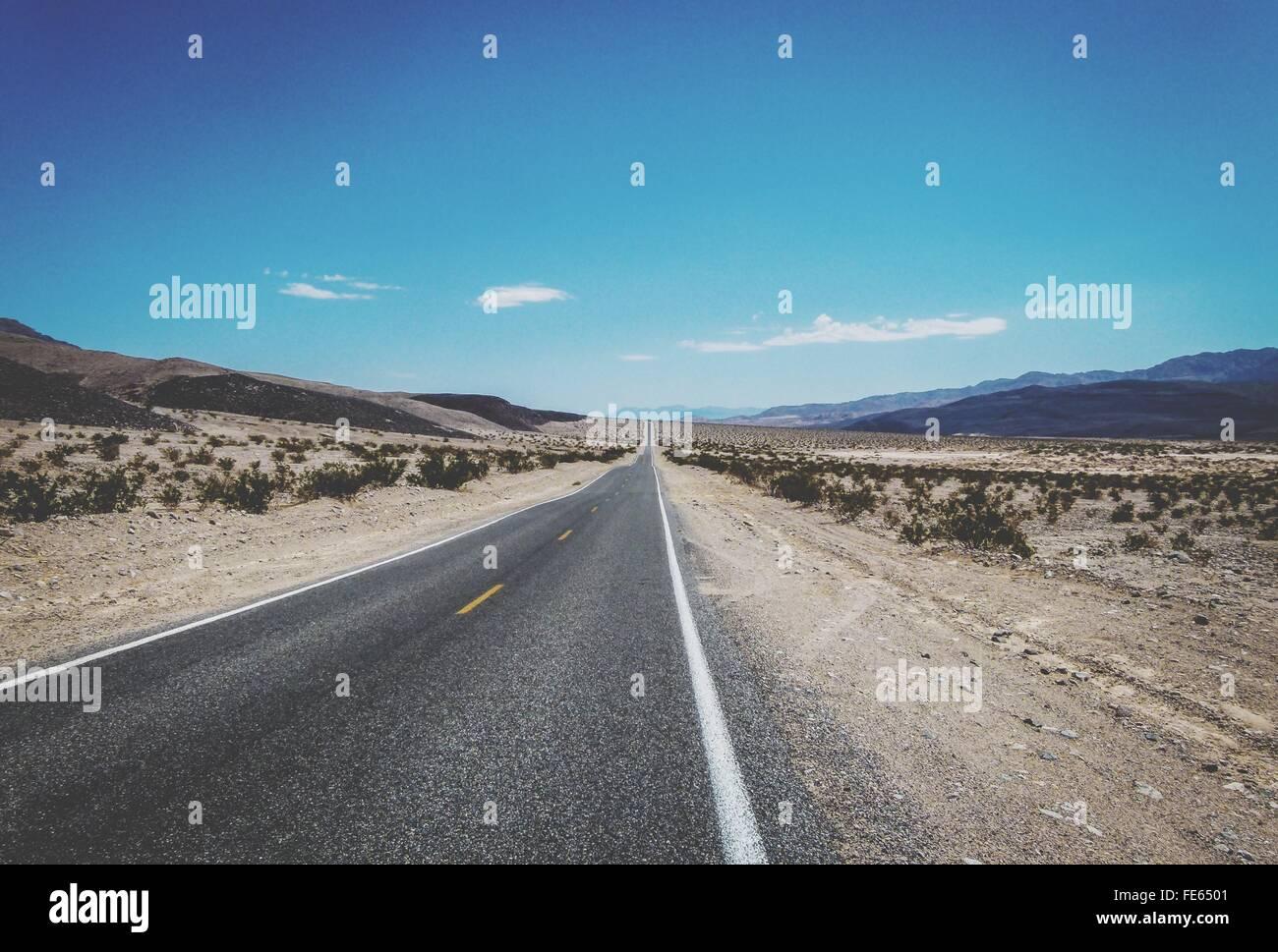 Empty Desert Road Against Blue Sky - Stock Image