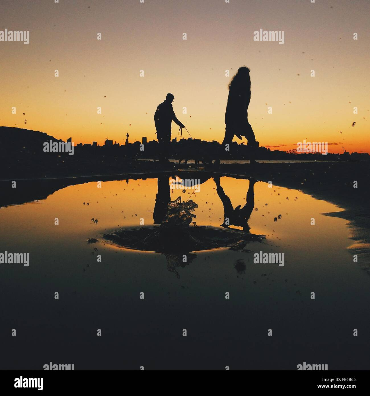 Silhouette Of Two People Walking At Lakeside At Sunset - Stock Image