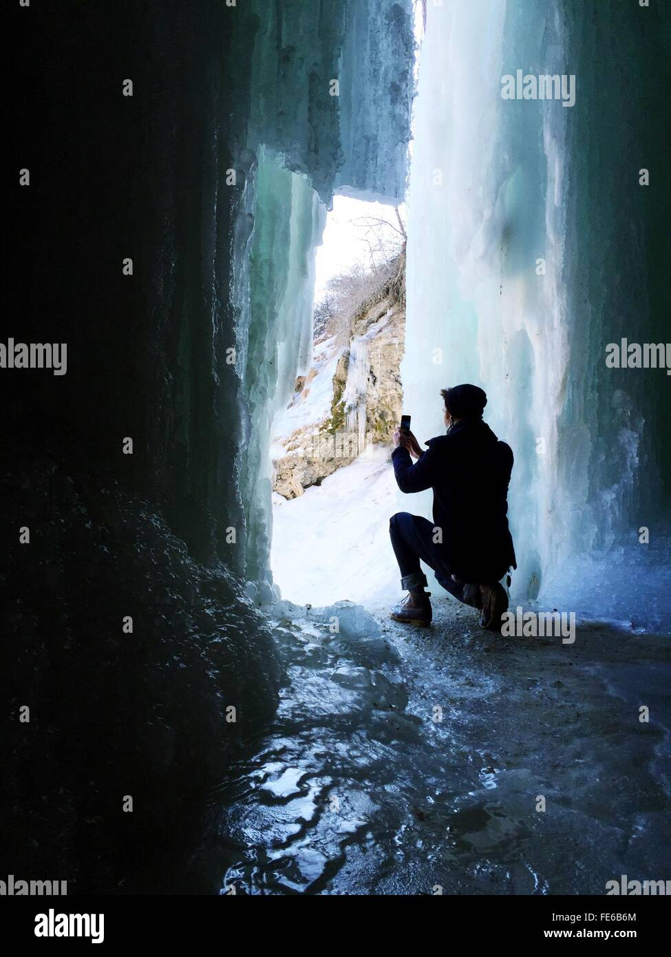 Rear View Of Man Photographing Frozen Waterfall - Stock Image
