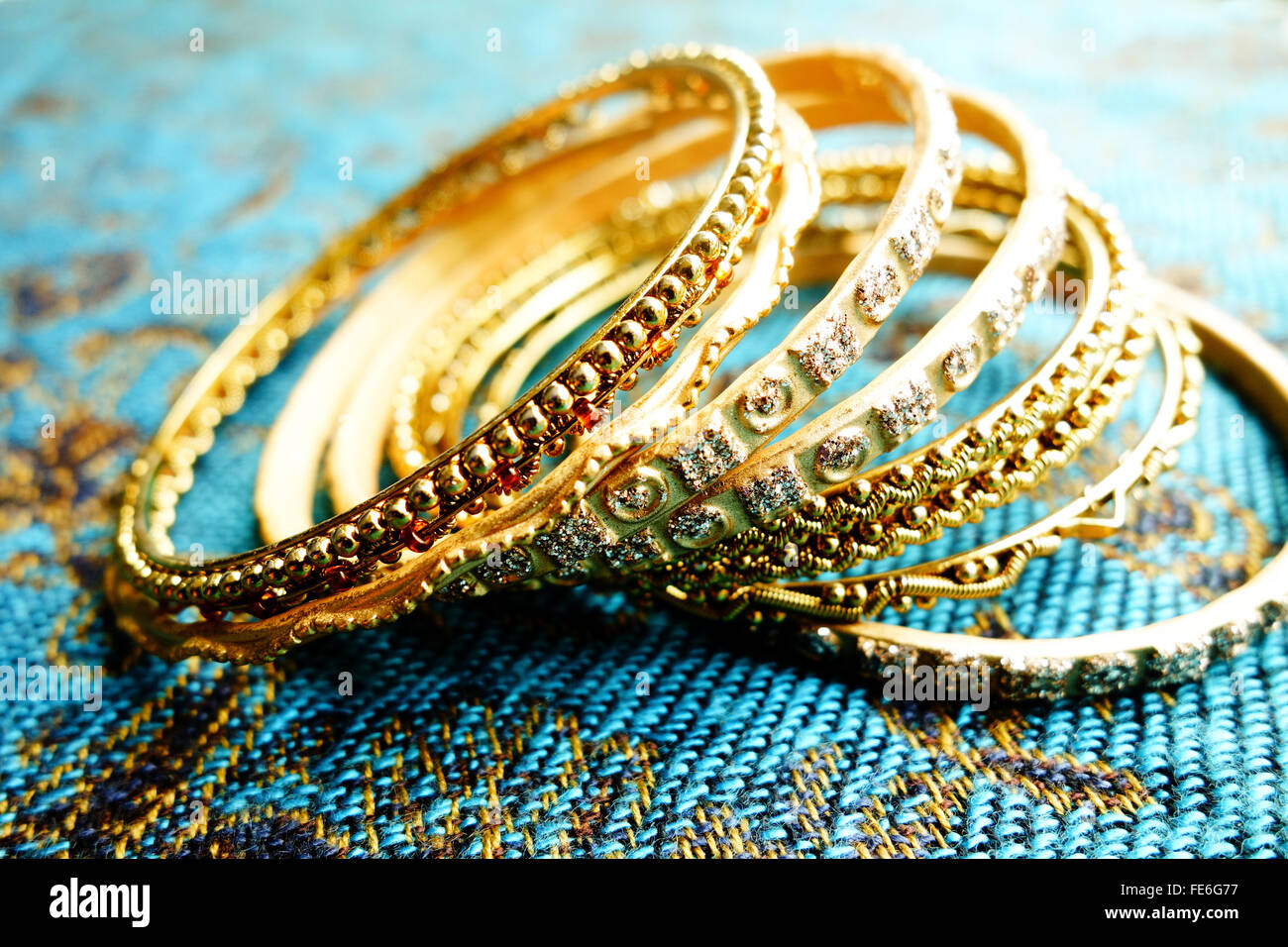 Close-Up Of Gold Colored Bangles On Blue Mat - Stock Image