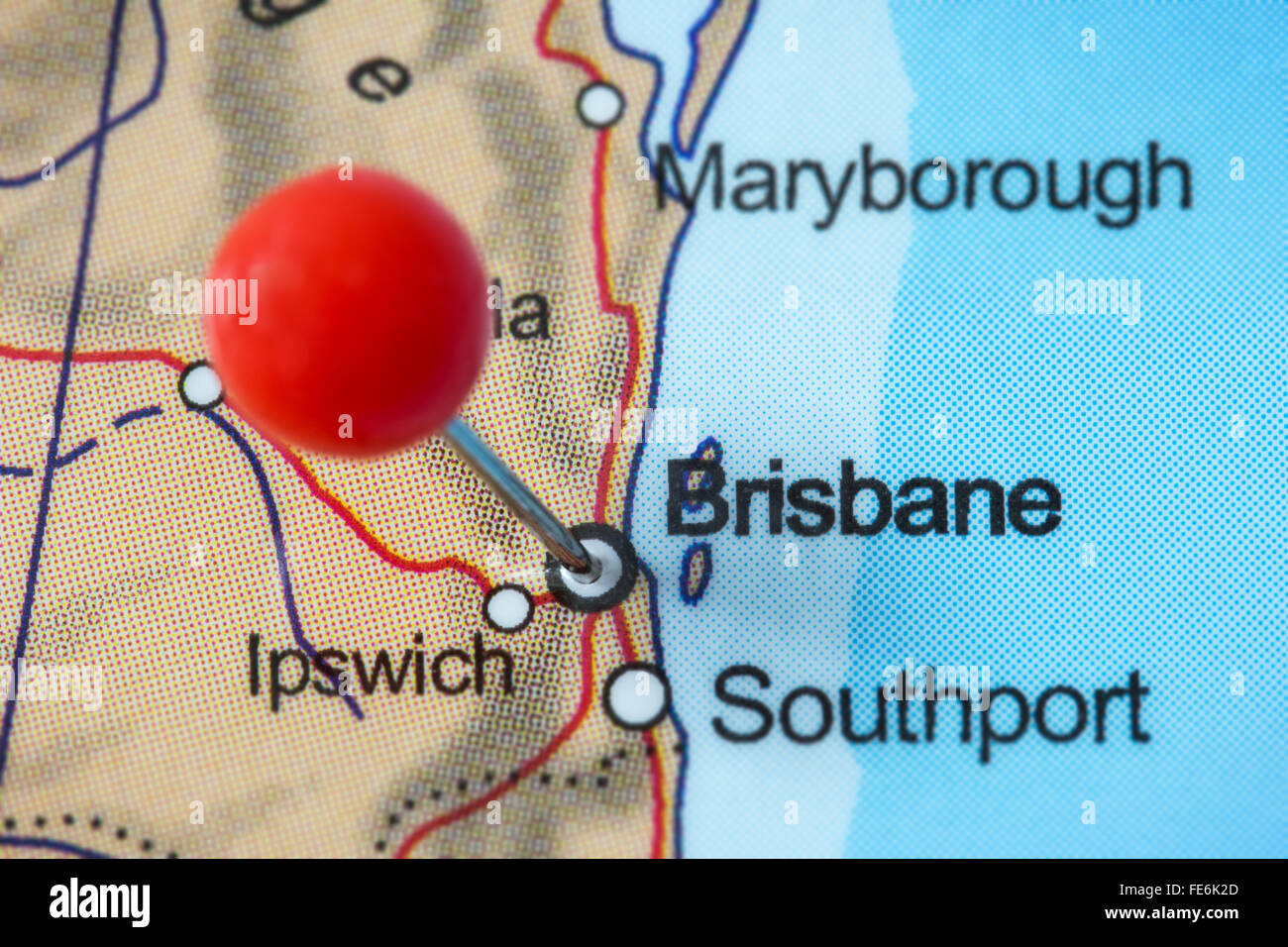 Close-up of a red pushpin in a map of Brisbane, Australia. - Stock Image