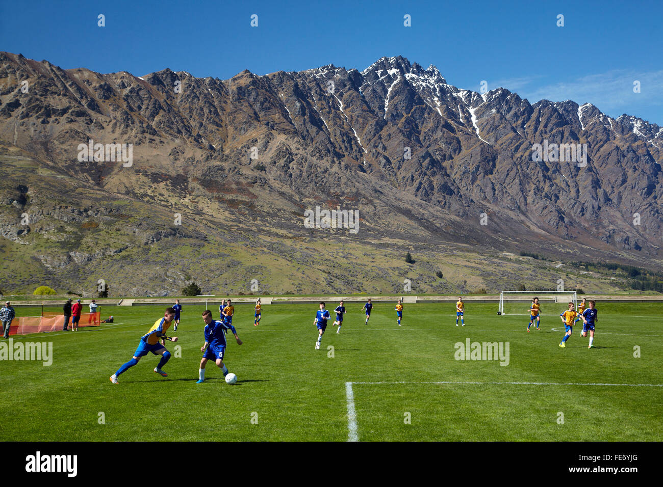 Otago play Nelson at the 13th Grade South Island Football Tournament, beside The Remarkables mountains, Queenstown, - Stock Image