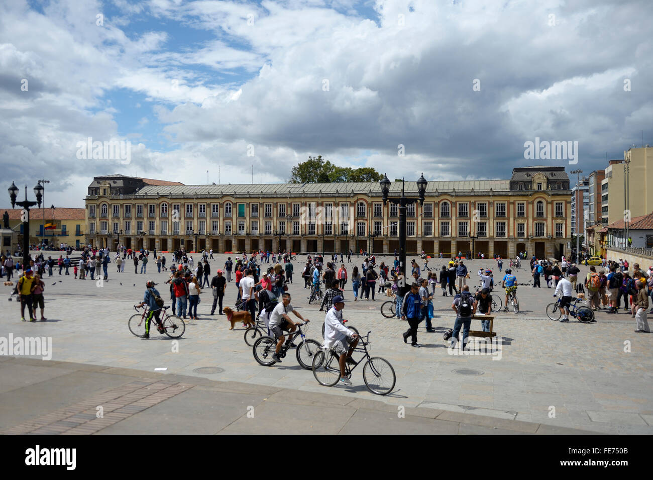 Cyclists a nd passersby in front of Palacio Liévano, mayor's office and city council, Plaza Bolivar, Bogota, - Stock Image