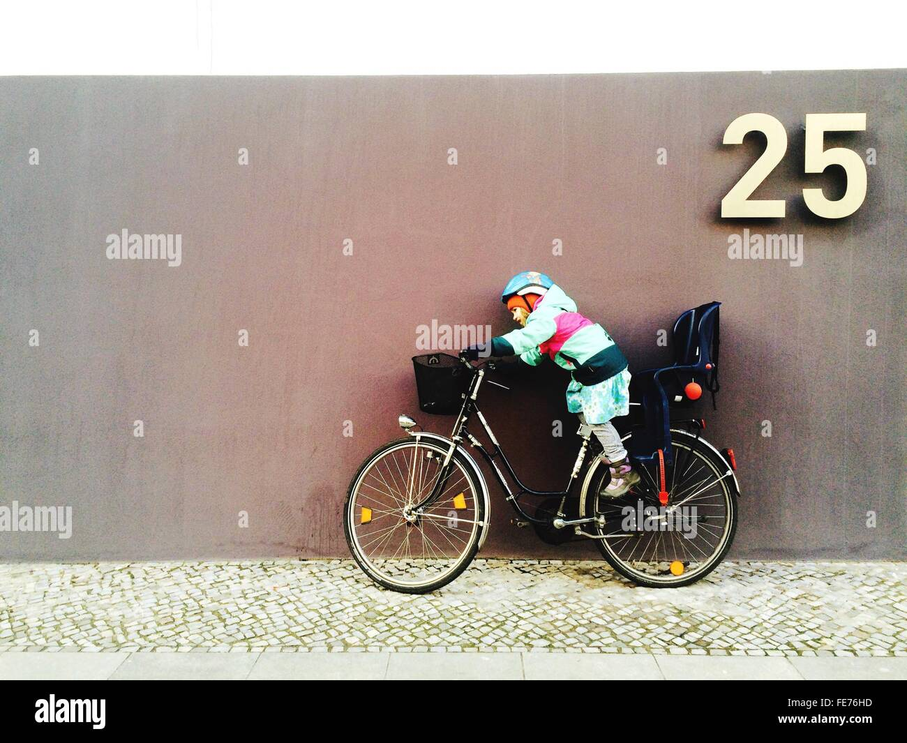 Boy On Bicycle Against Wall - Stock Image