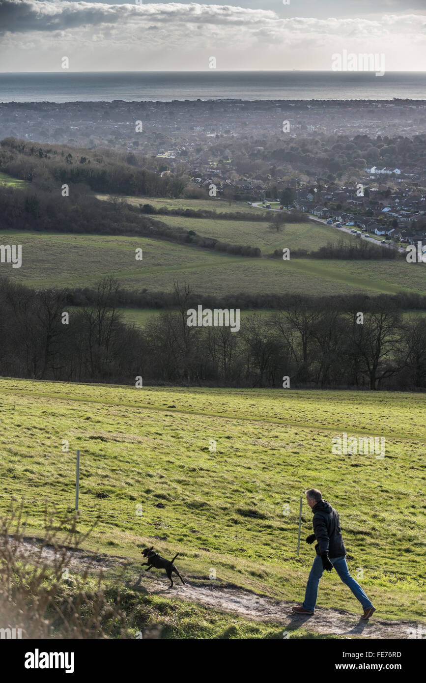 A man walking a dog on Cissbury Ring hill fort in Findon, West Sussex. - Stock Image