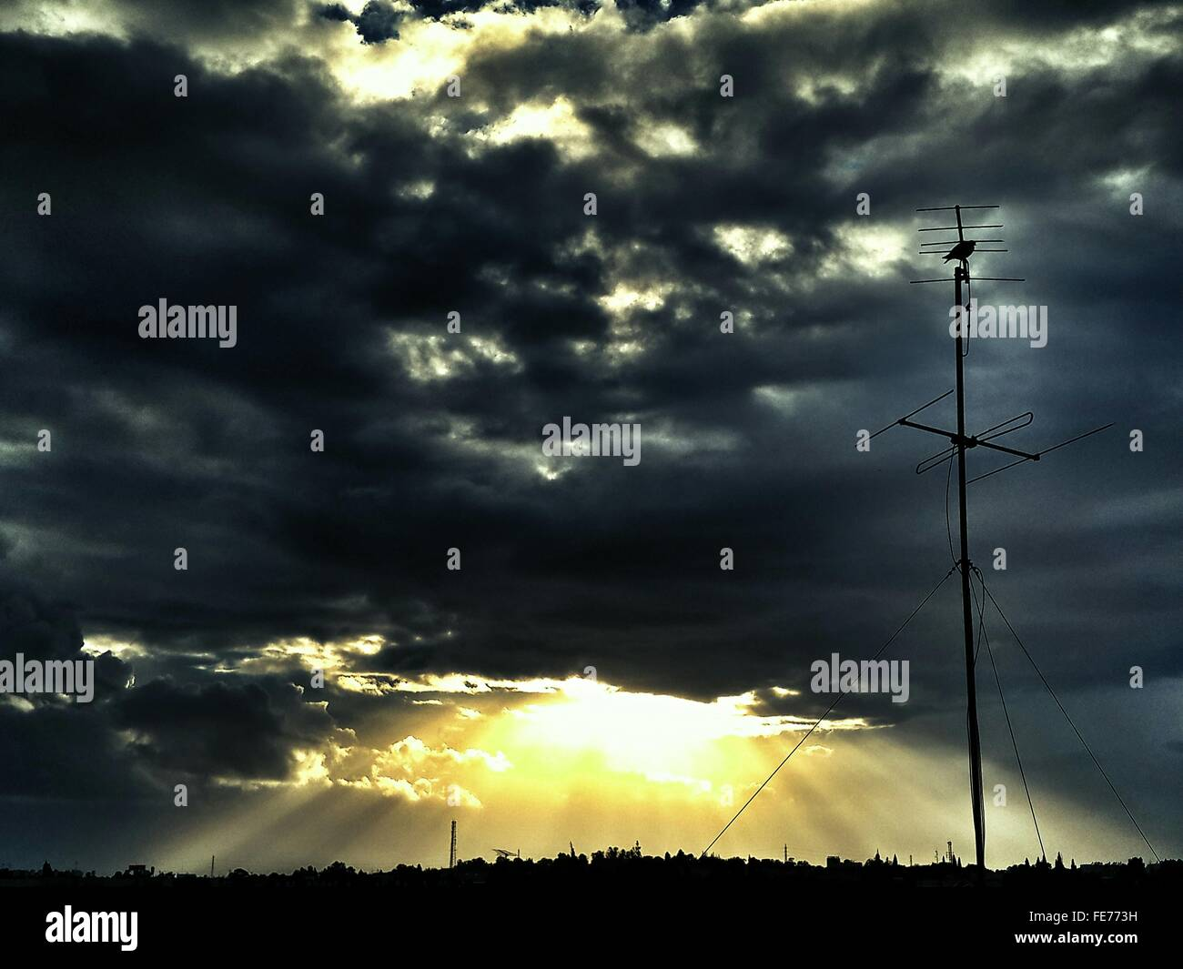 Low Angle View Of Silhouette Television Aerial Against Cloudy Sky During Sunset - Stock Image