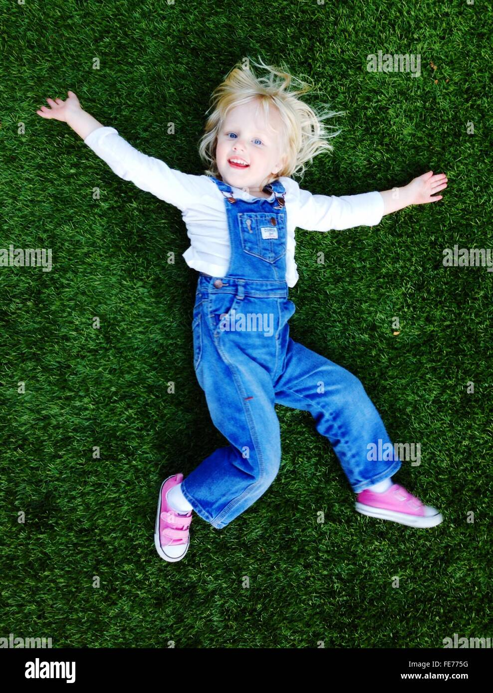High Angle Portrait Of Smiling Cute Girl Relaxing On Grassy Field Stock Photo