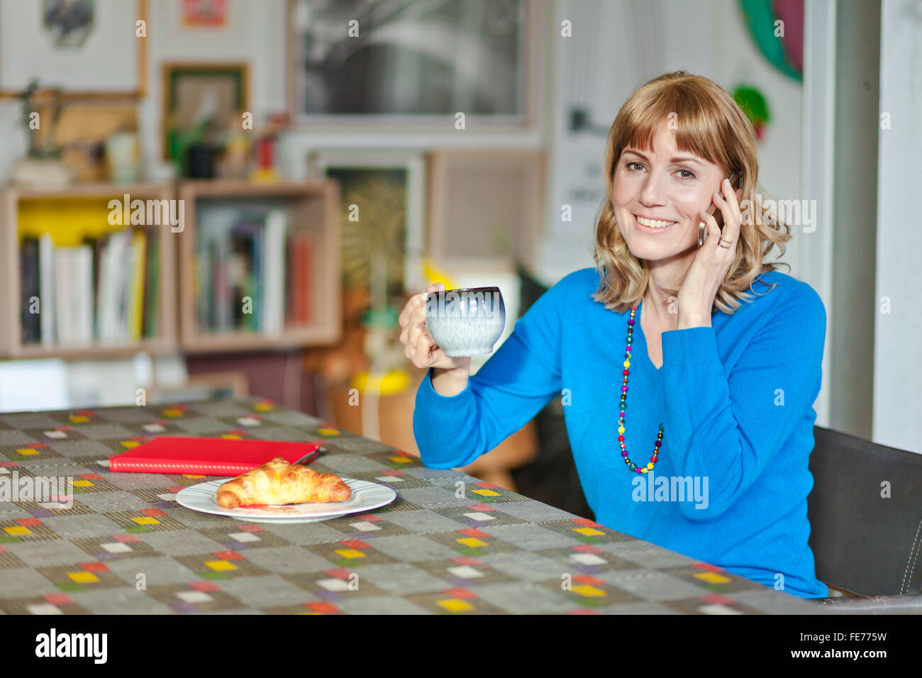 Woman talks on the phone at the living room table. - Stock Image