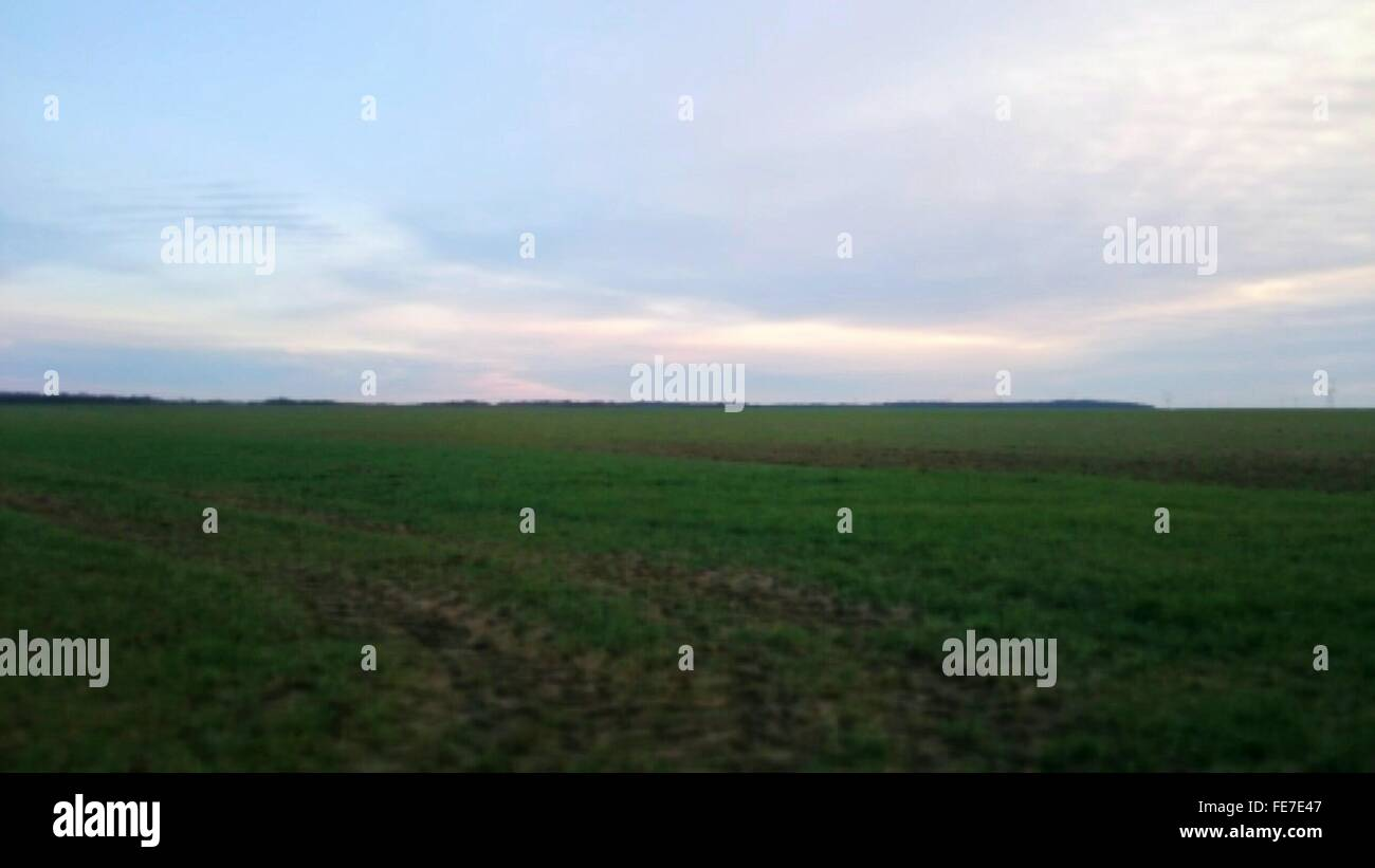 View Of Grassy Landscape Against Cloudy Sky Stock Photo
