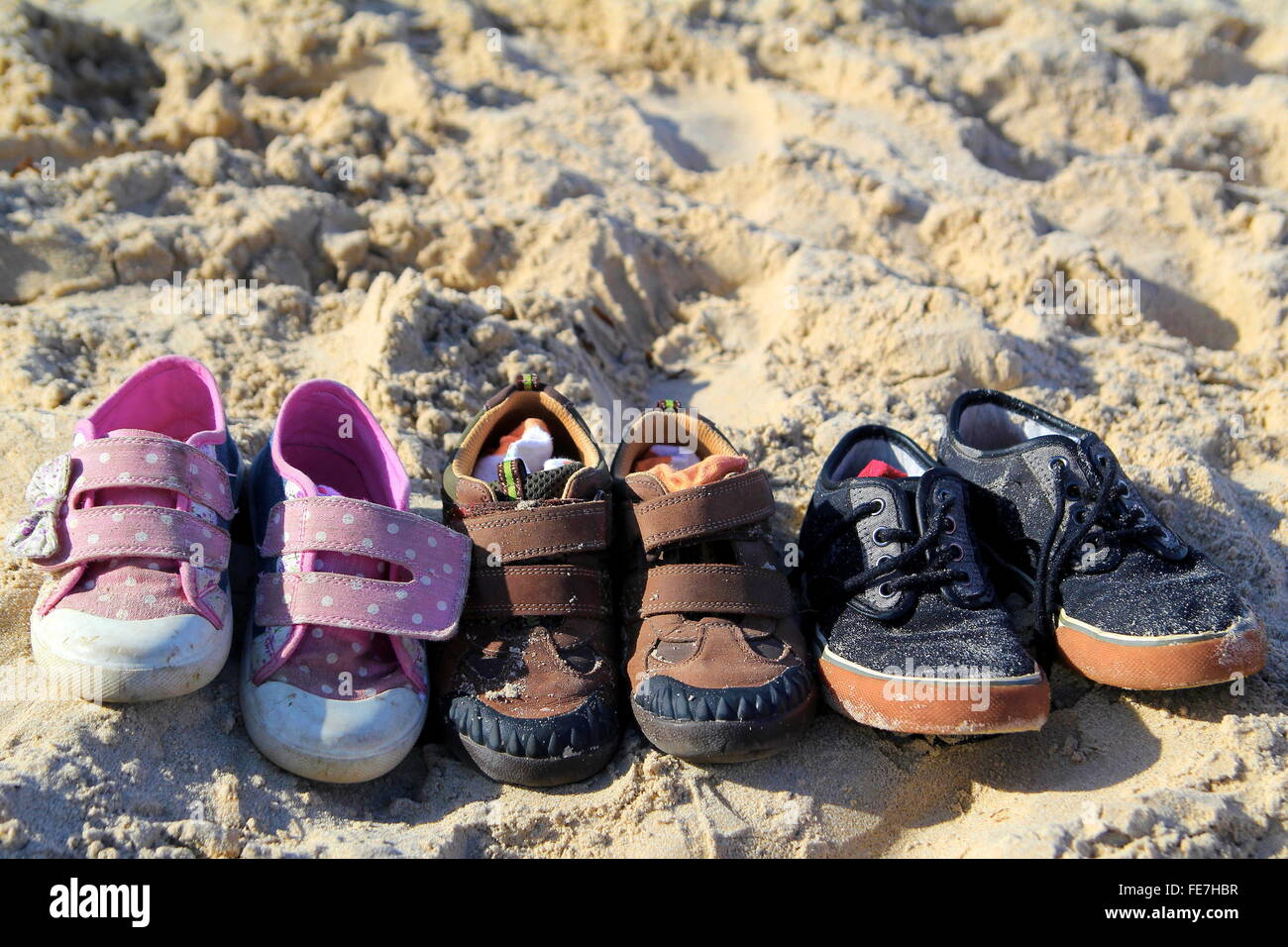 484109530cf8e Three pairs of childrens shoes and socks neatly left on a sunny beach