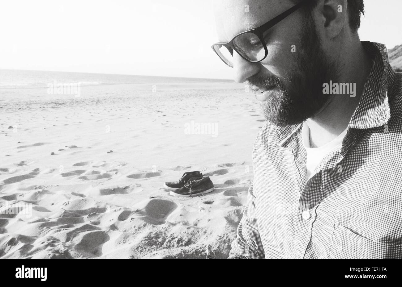 Side View Of Young Man Looking Down While Standing At Beach - Stock Image