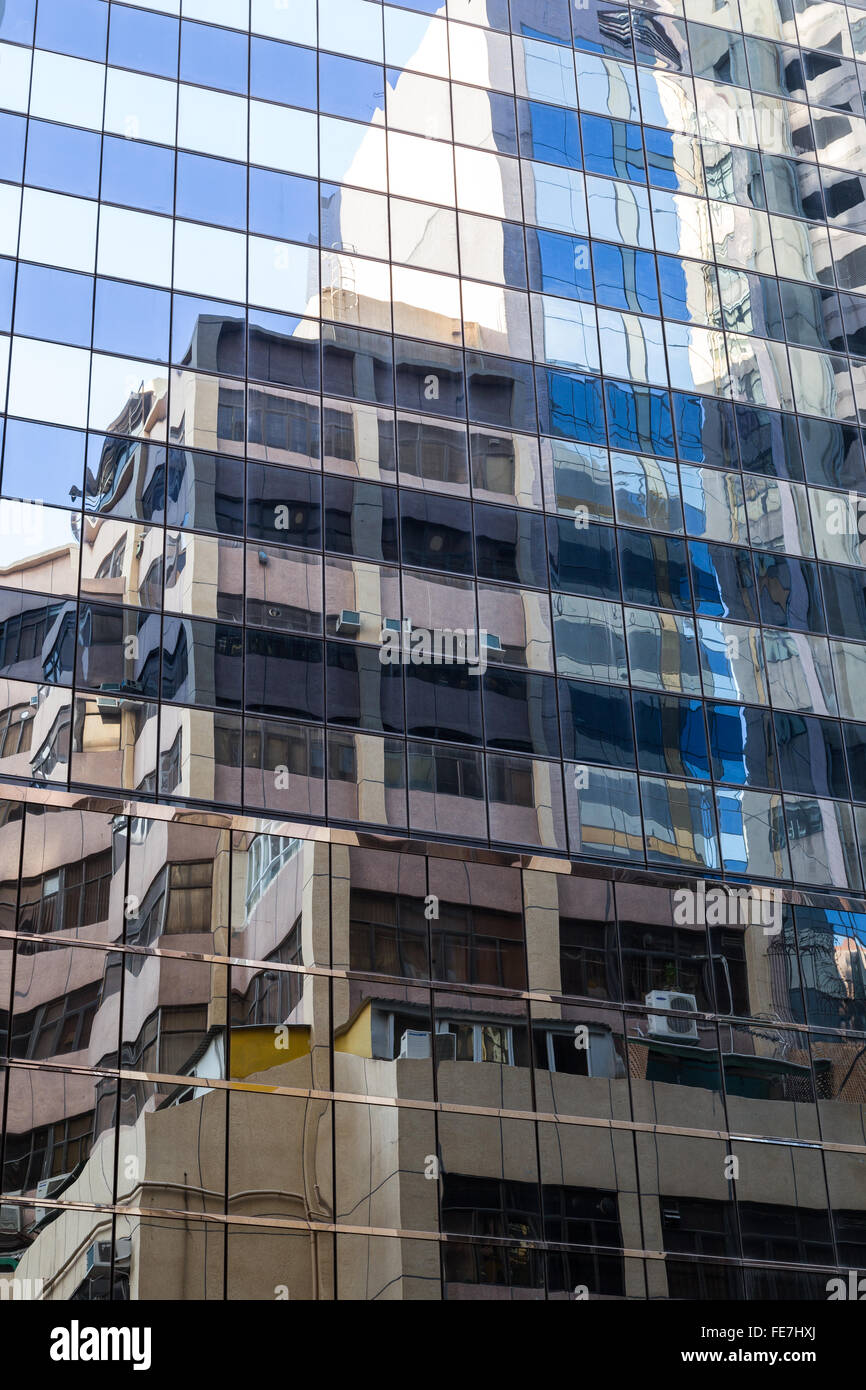 Skyscraper's glass wall and reflection of another buildings on it. - Stock Image