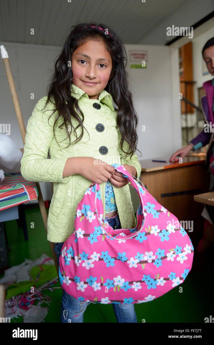 Girl proudly displaying her homemade bag, vocational training, Creciendo Unidos social project, Javier Villa, Bogotá, - Stock Image