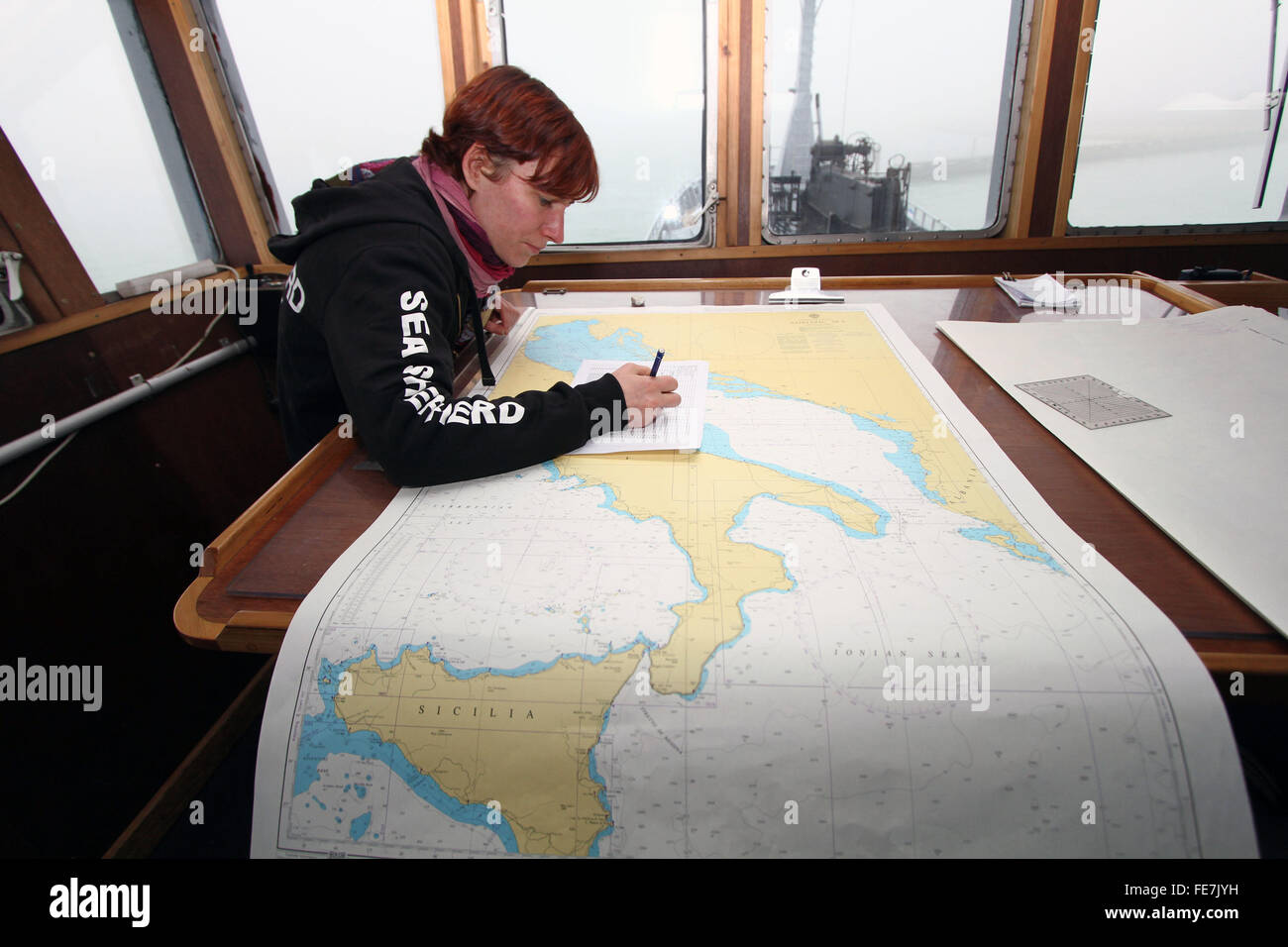 Venice, Italy. 3rd February, 2016. A member of crew of the Bob Barker ship with navigation chart in the control - Stock Image