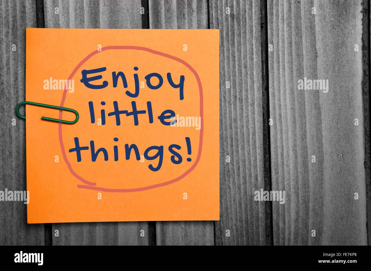 Enjoy little things word on orange notes - Stock Image