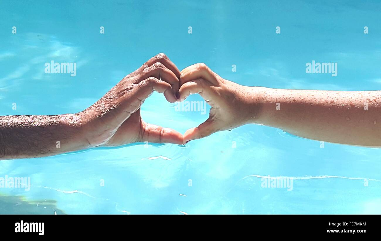 Close-Up Of Hands Forming Heart Shape Against Blue Water - Stock Image