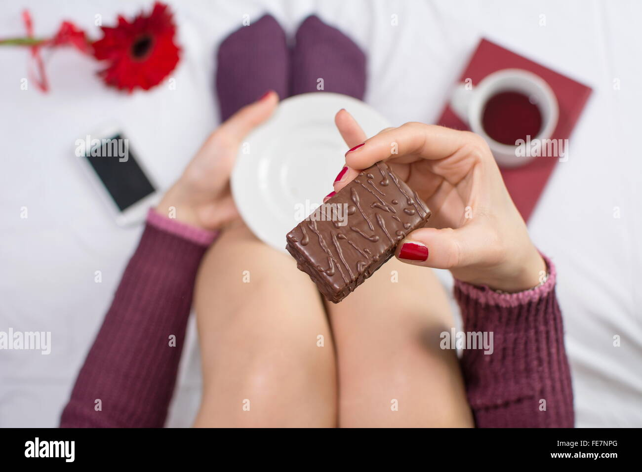 Girl having her sweet dessert in bed - Stock Image