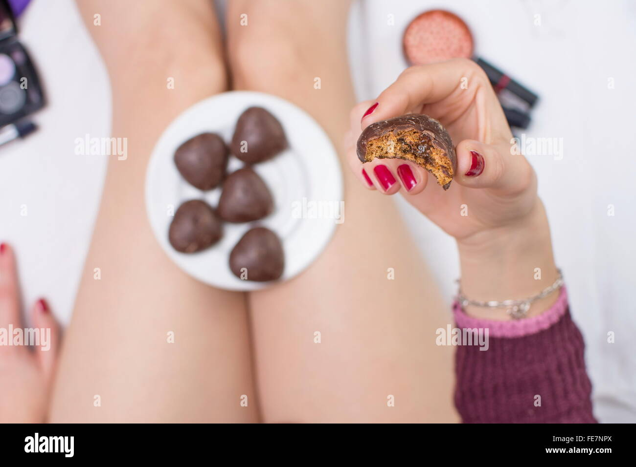 Girl eating her sweet dessert in bed - Stock Image