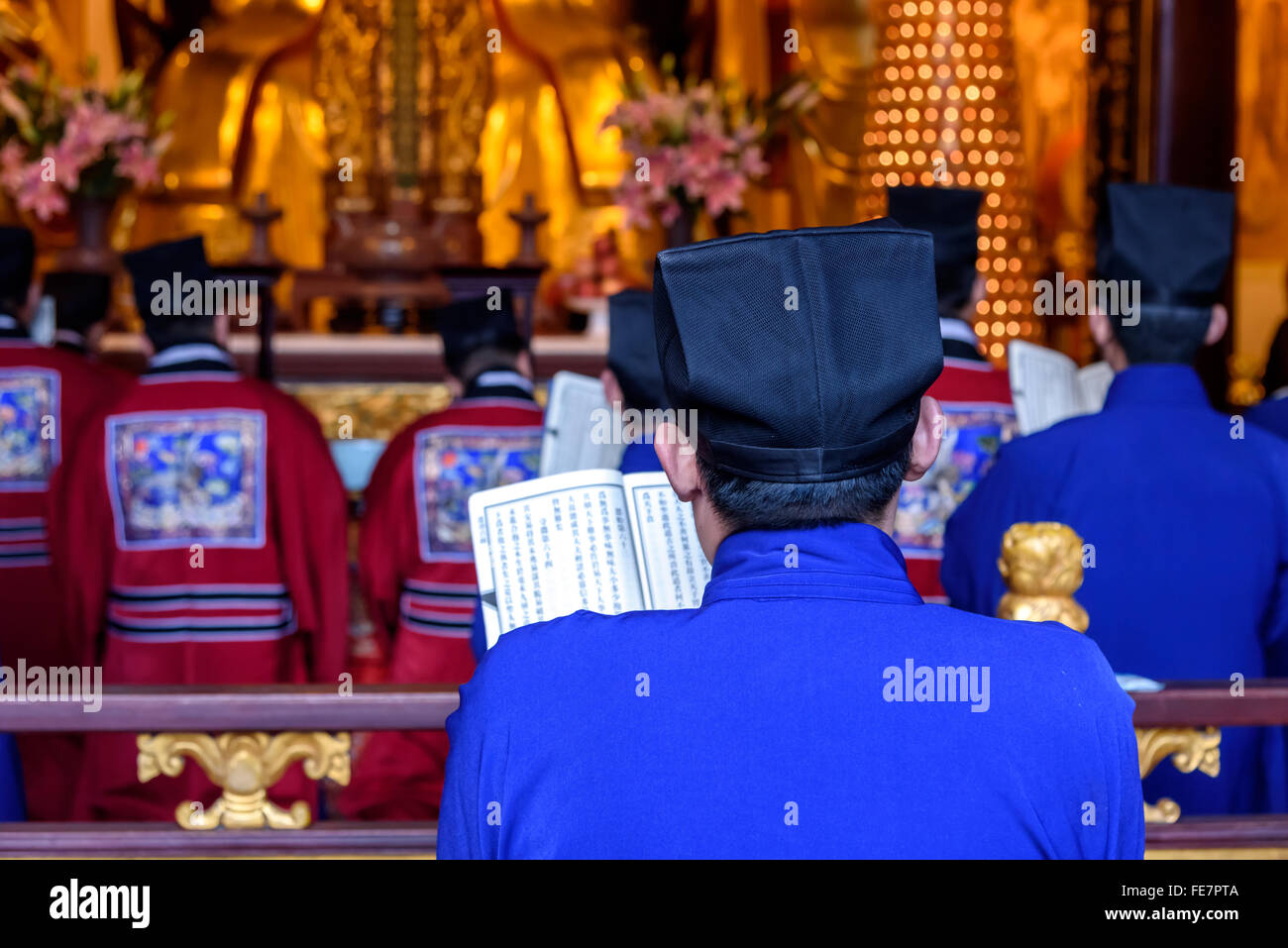 Chinese monks reciting the religious scripture in the temple. - Stock Image