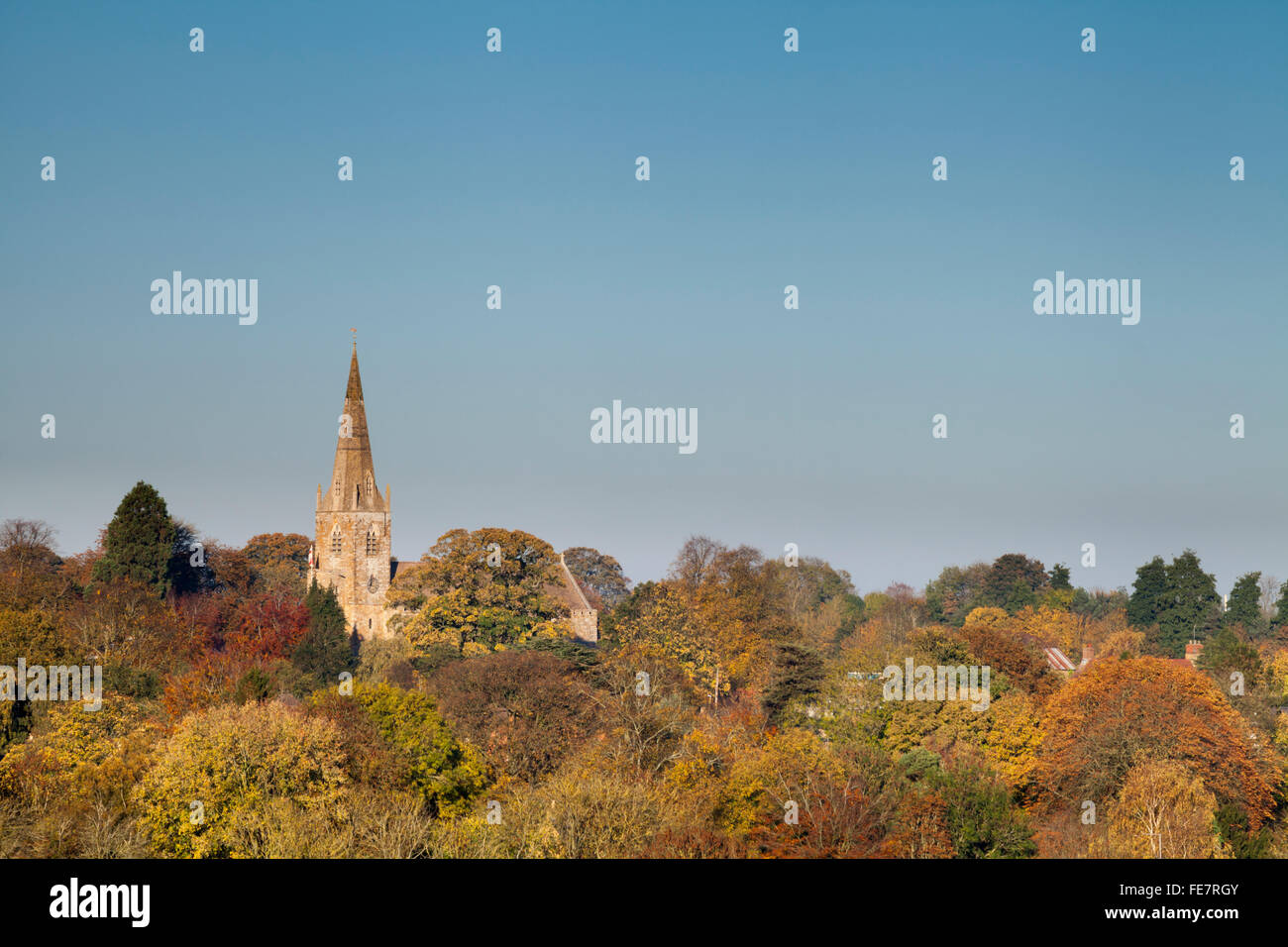 The Saxon church of All Saints rising above autumn trees in the village of Brixworth in Northamptonshire, England. - Stock Image