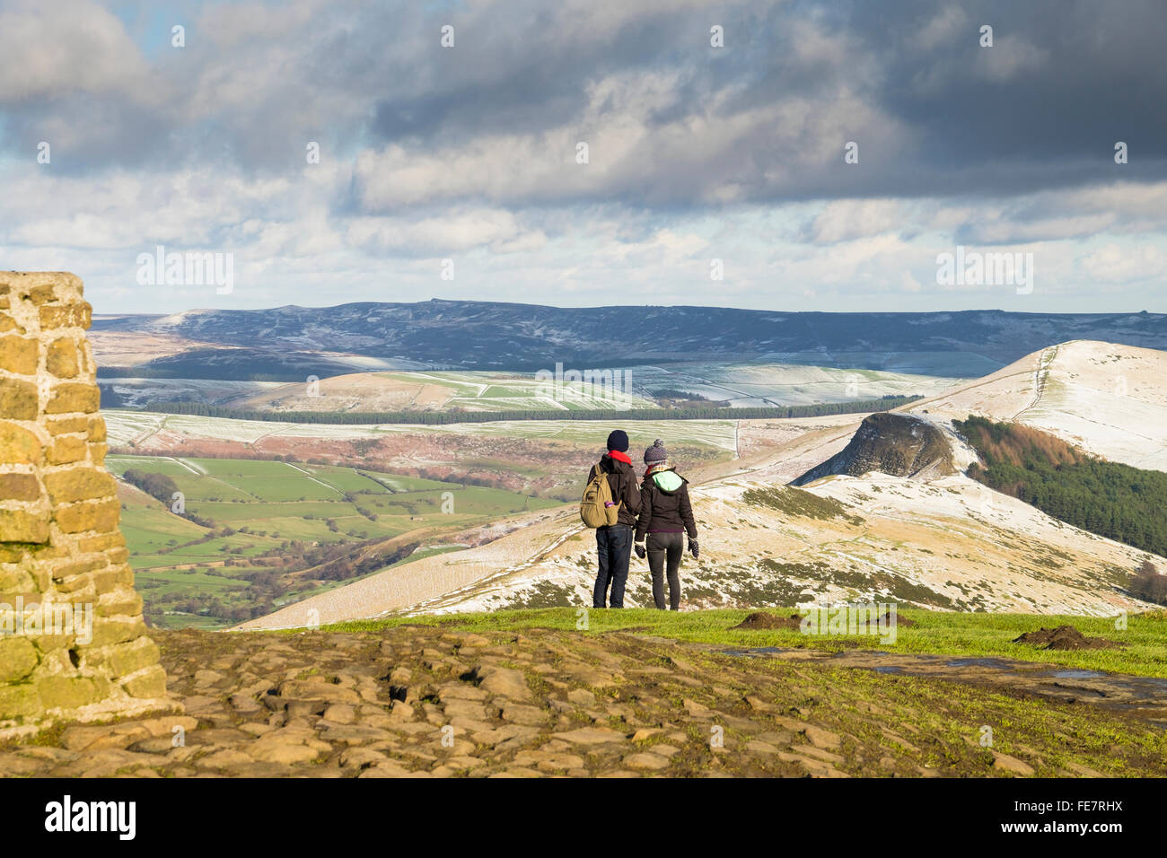 Walkers at the Trig point on the top of Mam Tor on a bright winter day. Stock Photo