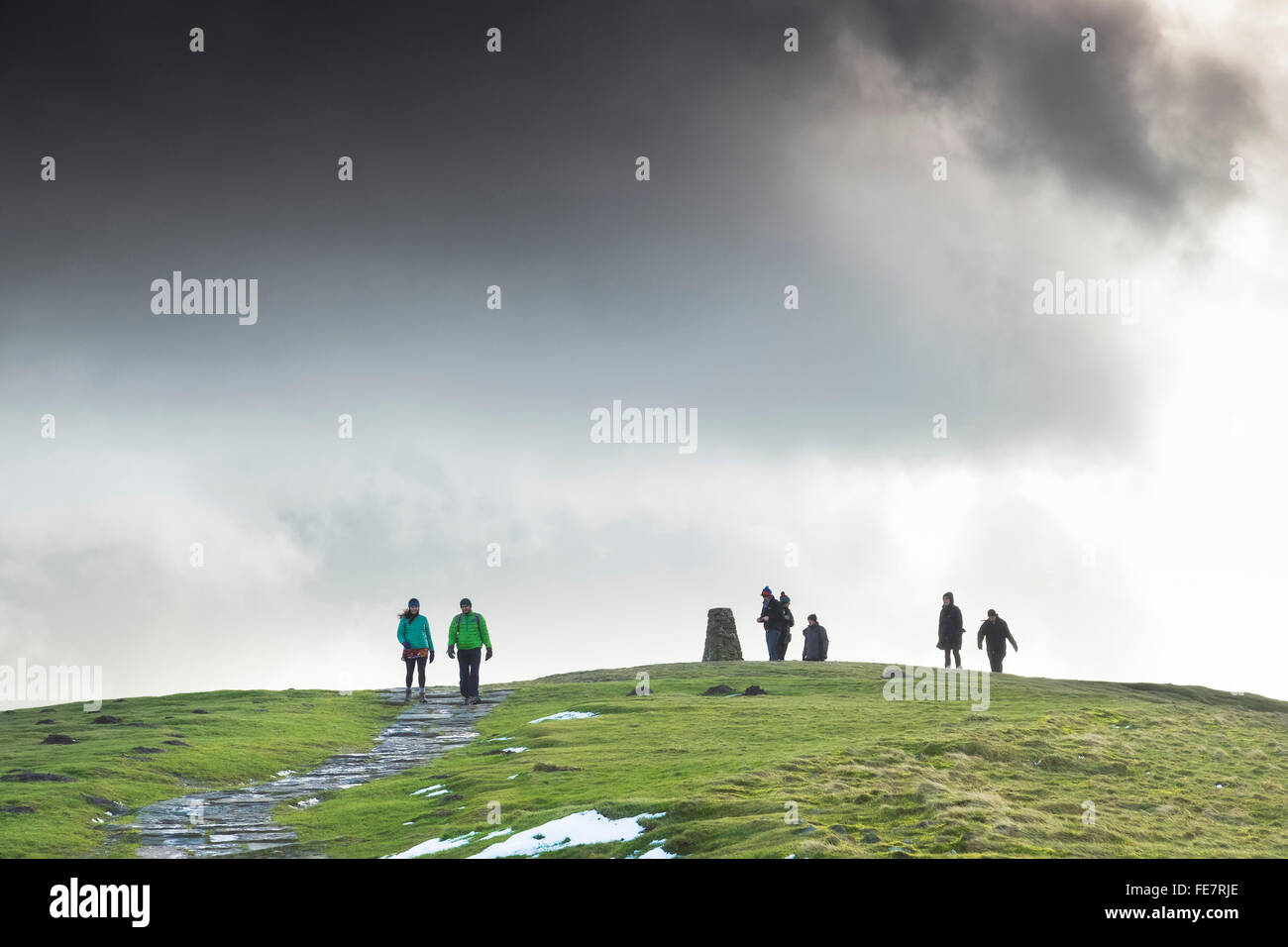 Walkers at the Trig point on the top of Mam Tor on a bright winter day. - Stock Image